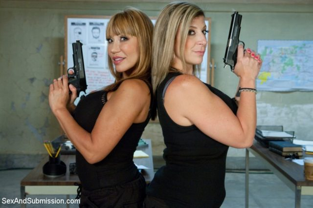 Sara Jay AdultWebcamSites - Hot busty blonde brunette MILF pornstar Sara Jay and Ava Devine in sexy black dresses with guns - Kink.com Sex & Submission The Big Bust 2 Drug Lords Take Revenge BDSM feature update Sara Jay porn pics sfw